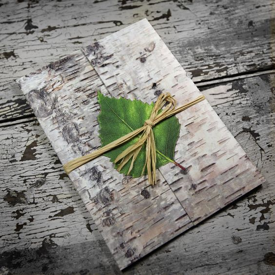 birch bark invitation topped with a green leaf