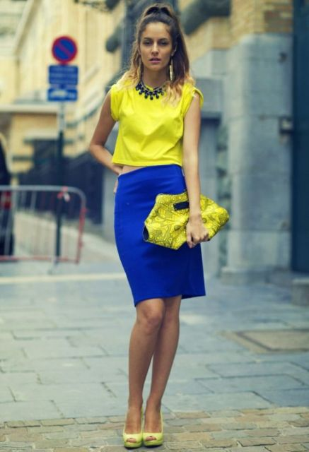 With yellow top, black necklace, yellow shoes and yellow printed clutch