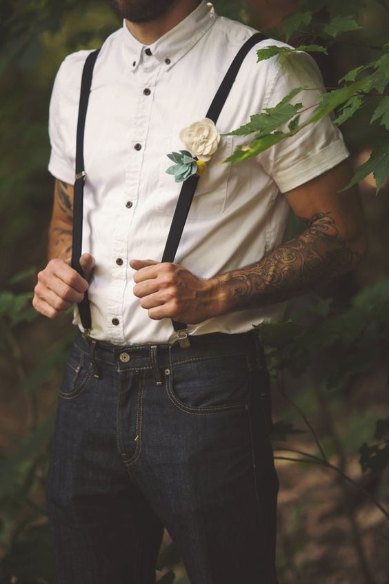 black jeans, an ivory short sleeve shirt with black buttons and black suspenders