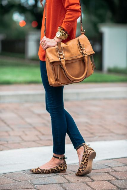 With red shirt, brown leather bag and skinny jeans