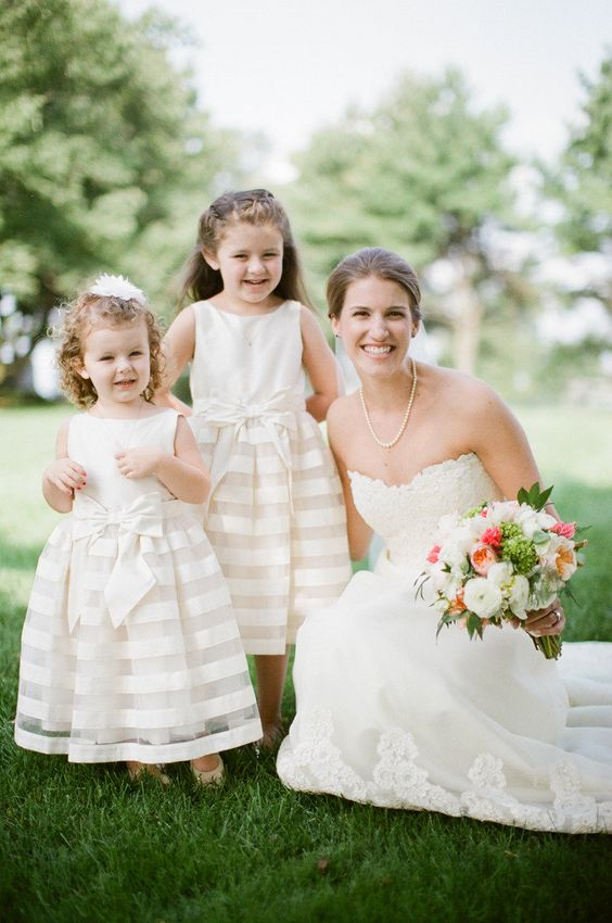 sleeveless ivory dresses with striped skirts and bows on the waist