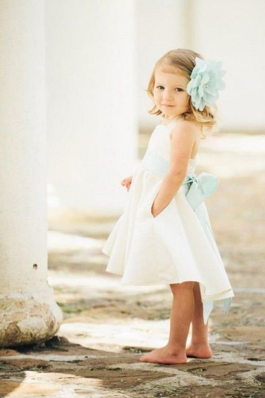 high low ivory dress with a mint sash and a large mint flower in the hair