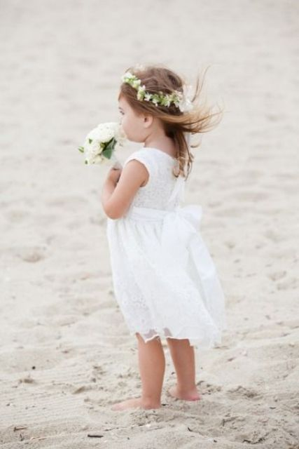 a white lace sleeveless dress and a white floral crown