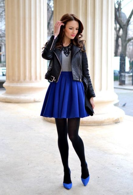 With gray shirt, black leather jacket, black tights and blue shoes
