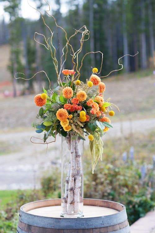 a tall vase with birch branches and a bold fall-inspired floral arrangement