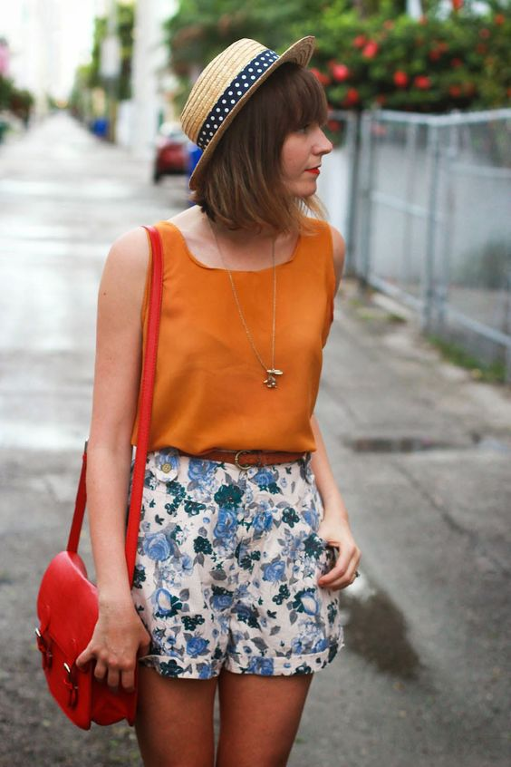 a bold orange sleeveless top and blue floral shorts