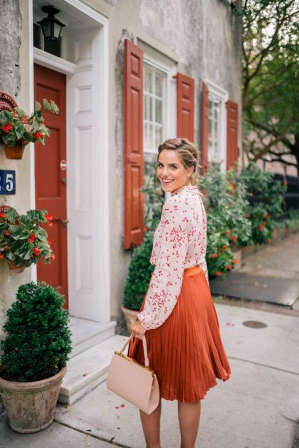 With floral blouse and pale pink bag