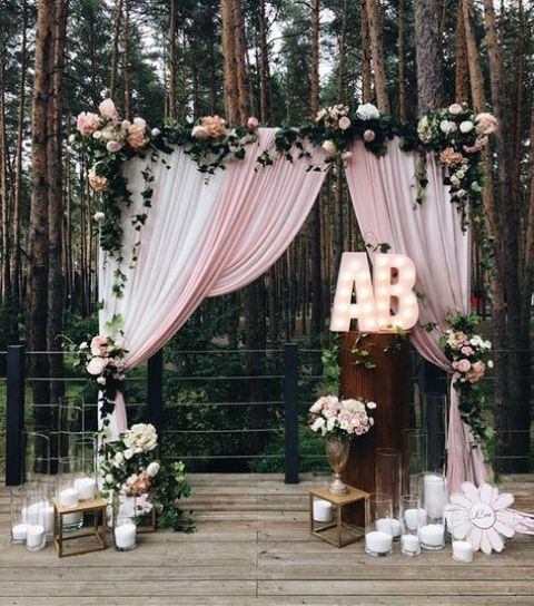 cute altar with pink curtains, pink and blush flowers, candles and marquee letters