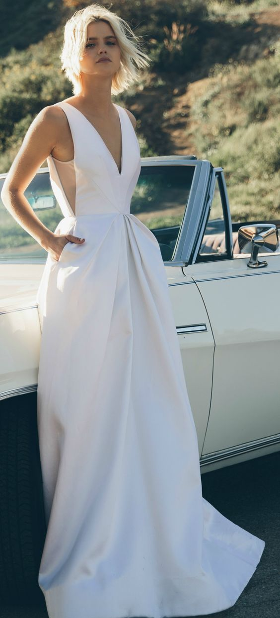 modern wedding dress with pockets made from couture silk with hand pleated panels and a plunging neckline