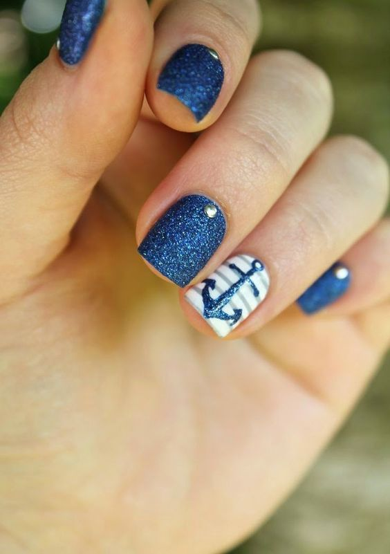 navy glitter nails with rhinestones and a striped accent nail with an anchor