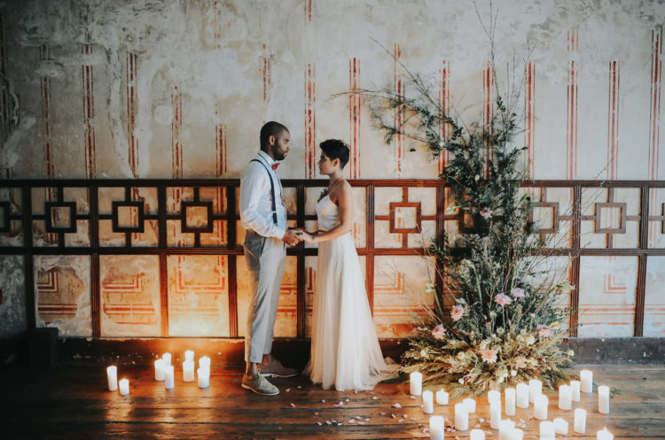 The ceremony space was industrial yet softened with greenery, flowers and lots of candles