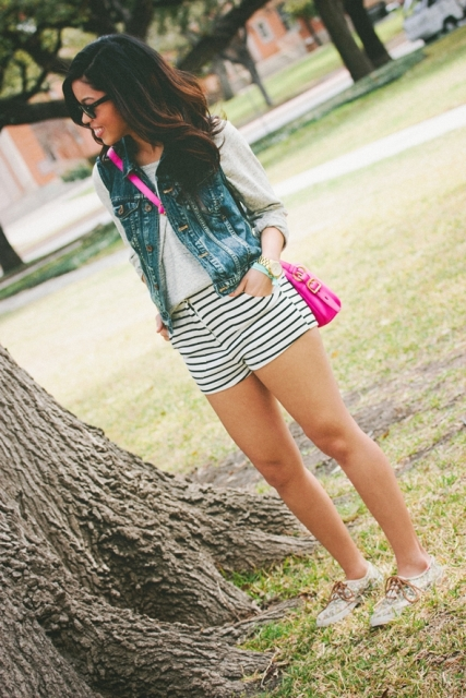 With white shirt, denim vest, hot pink bag and printed sneakers
