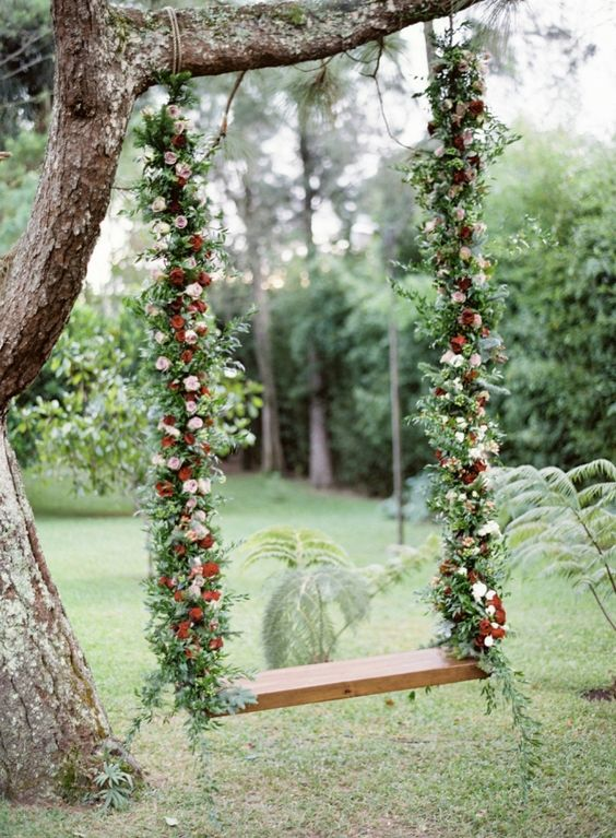 fall-inspired swing with greenery and pink and red flowers