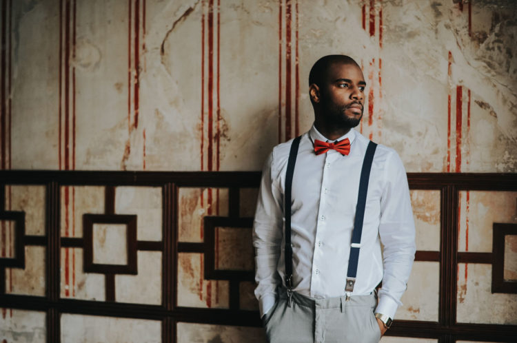 The groom was wearing grey pants, a white shirt, navy suspenders and a red bow tie