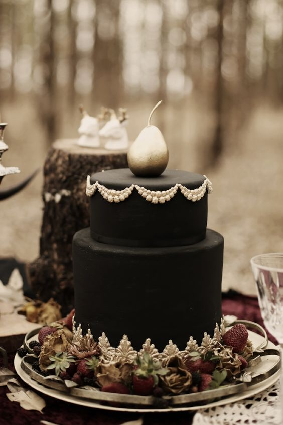 black wedding cake with white cream decor and a silvered pea ron top