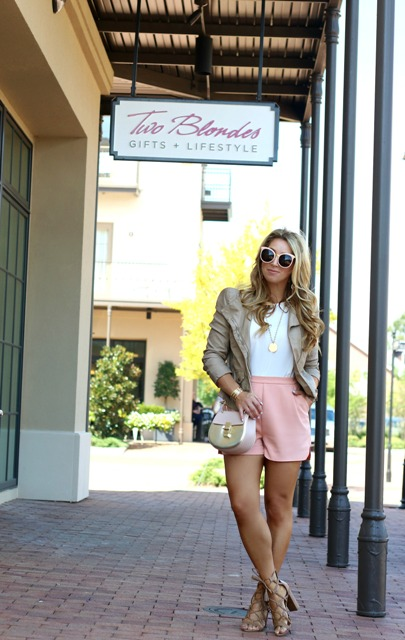 With white shirt, leather jacket, beige sandals and mini bag