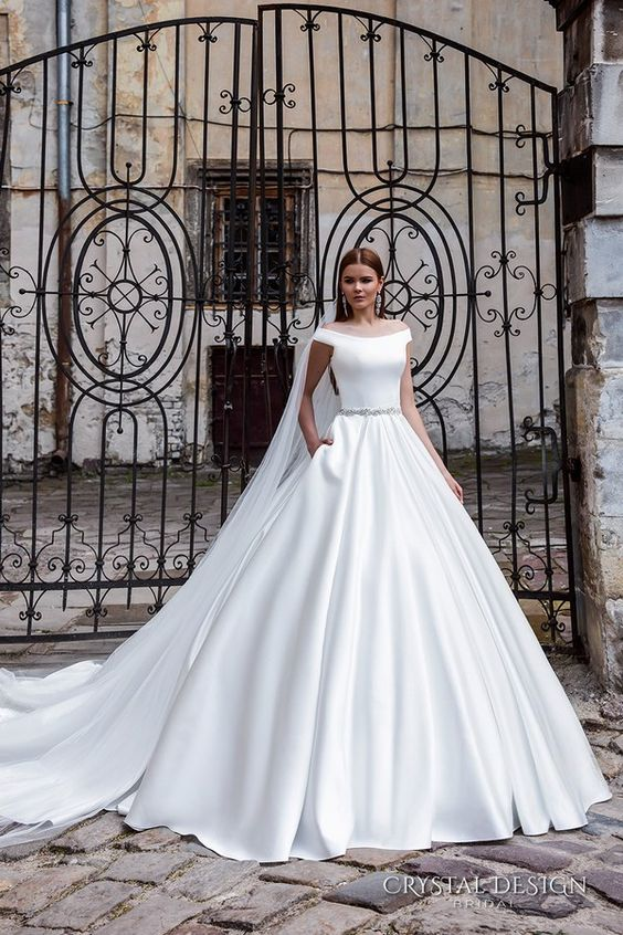 pure white off the shoulder ballgown with a train, an embellished sash and pockets