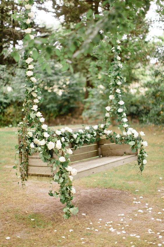 a swinging bench decorated with leaves and white blooms for the couple