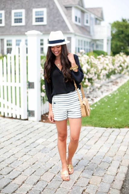 With black blouse, metallic sandals, beige bag and black and white hat