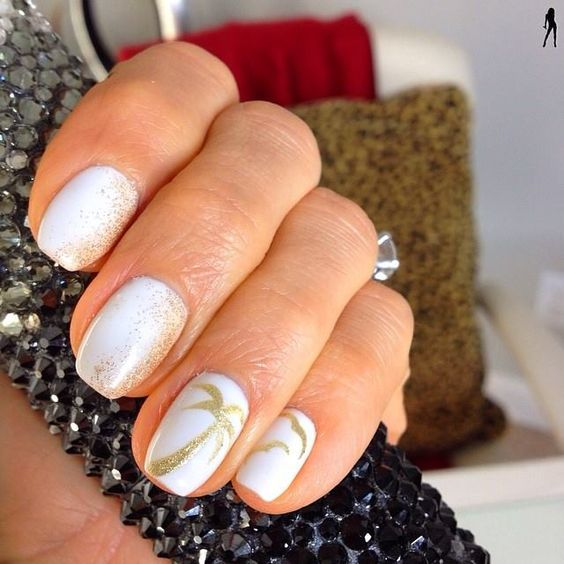 white nails with gold glitter imitating sand and palm trees