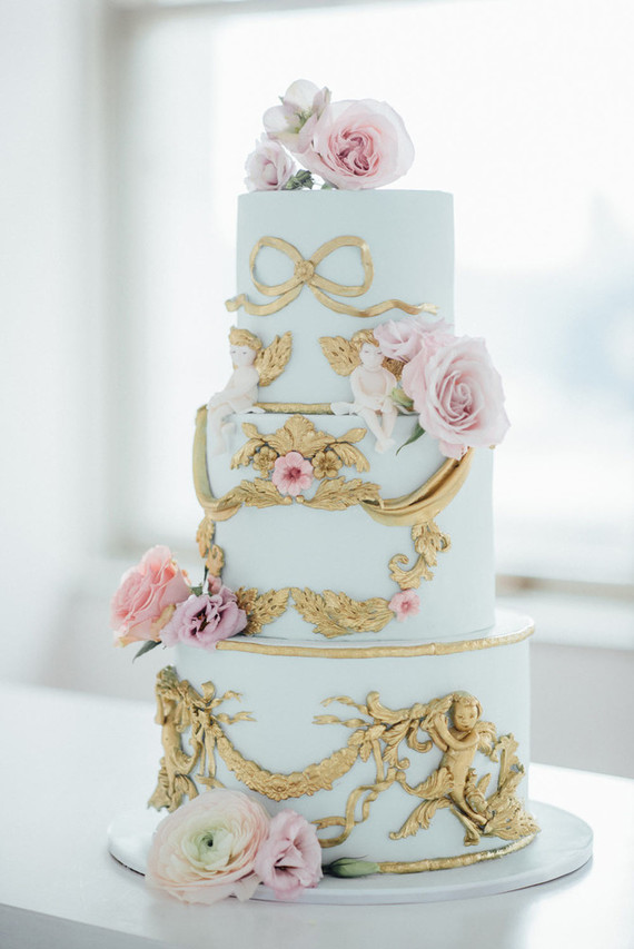 The wedding cake was done in aqua with fresh pink blooms and gold detailing