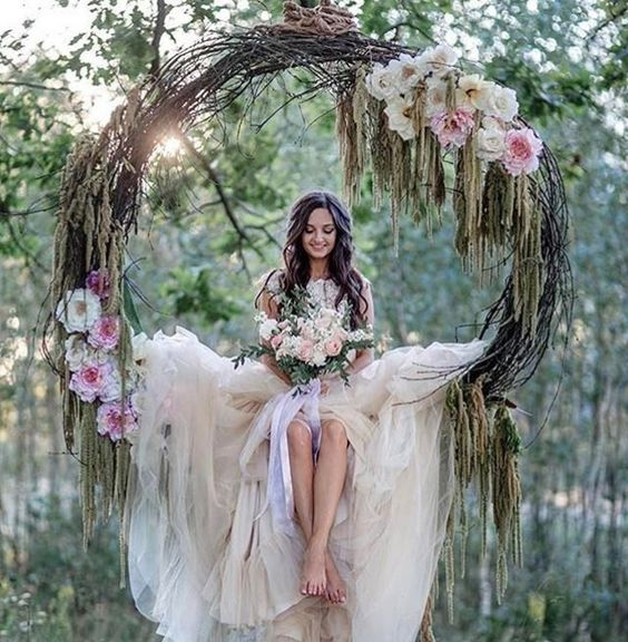 a grapevine wreath with pink flowers used as a swing for the bride