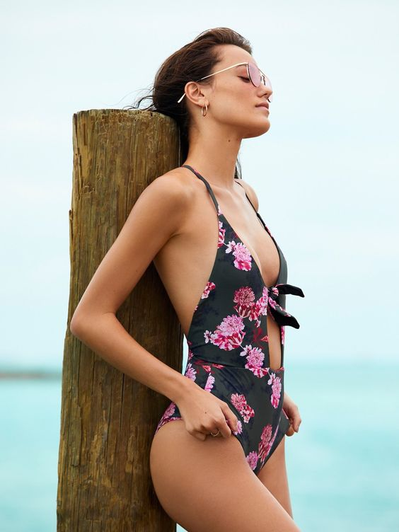black plunging neckline swimsuit with a pink floral print and a front cutout