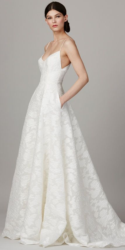 lace A-line wedding dress with a deep V neckline, spaghetti straps and pockets
