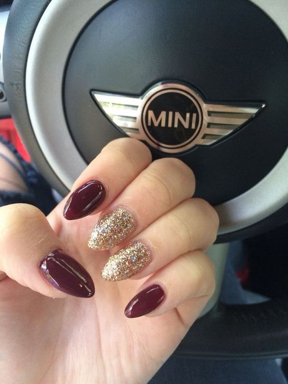 burgundy and gold glitter almond-shaped nails