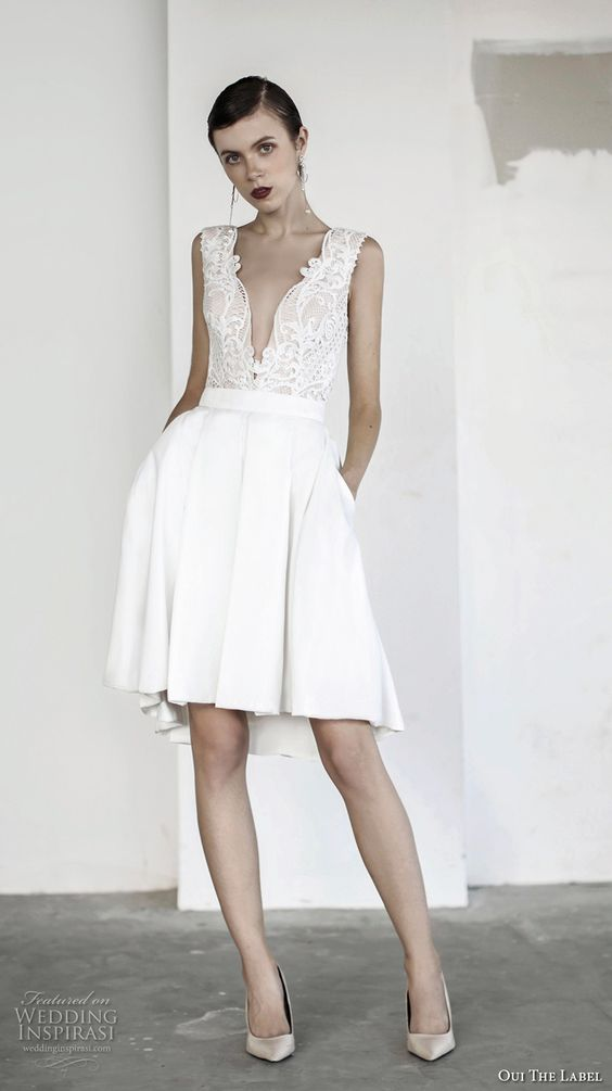 short wedding dress with a lace plunging neckline bodice and a pleated skirt with pockets