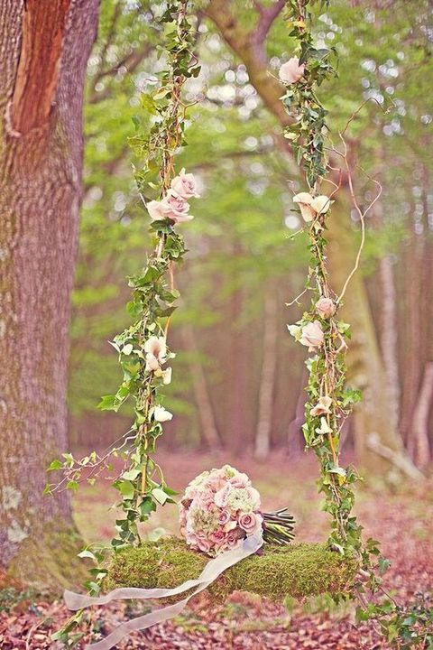 garden-inspired swing with pink roses, vine and a moss covered seat