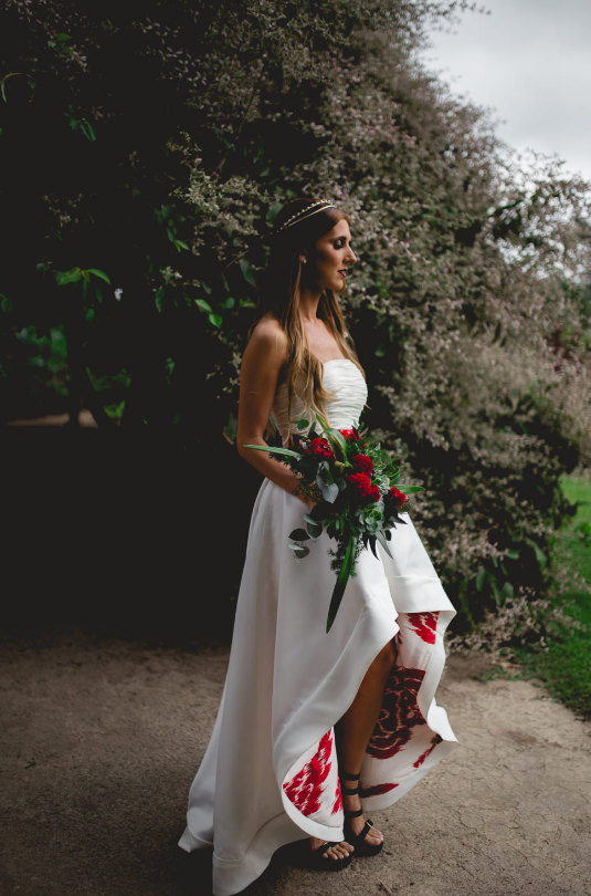 The wedding dress was designed especially for the bride, it was a strapless high low one with a bold sash and printed red lining