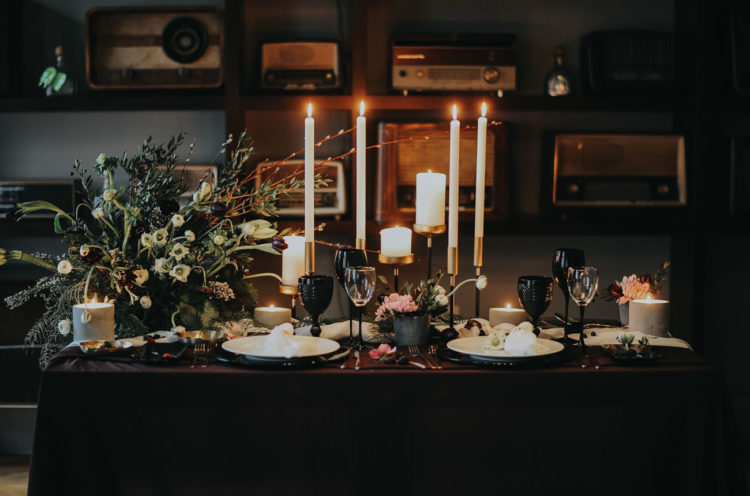 The sweetheart table was a dramatic one, with a textural floral centerpiece, candles, black glasses