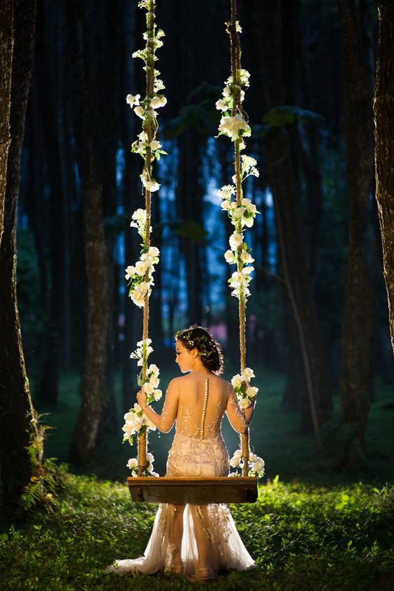 a swing decorated with white blooms is classics