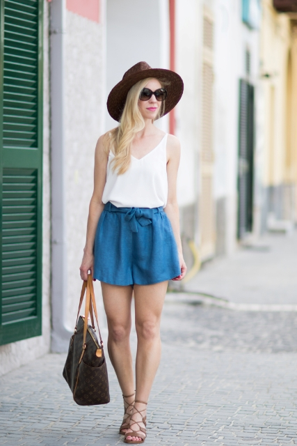 With white top, lace up sandals, brown hat and printed bag