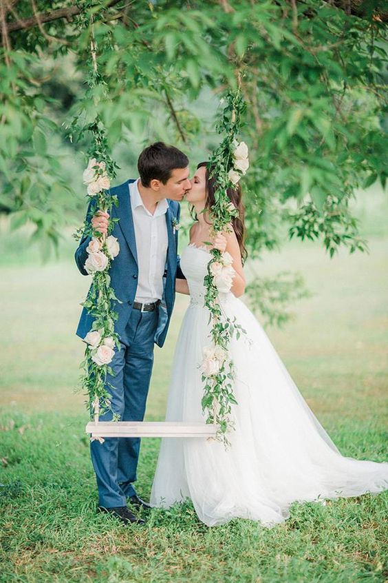 a gentle decorated swing with greenery and neutral blooms