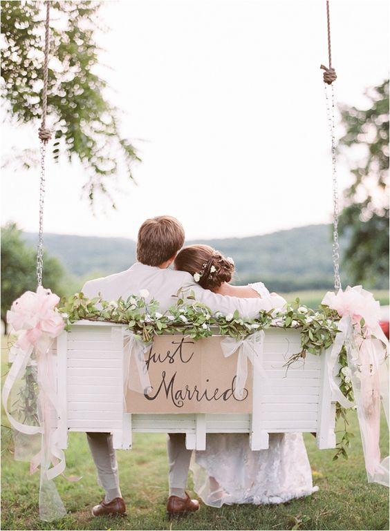a swinging bench decorated with greenery and blush fabric bows