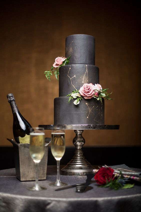 black wedding cake with gold constellation and fresh roses