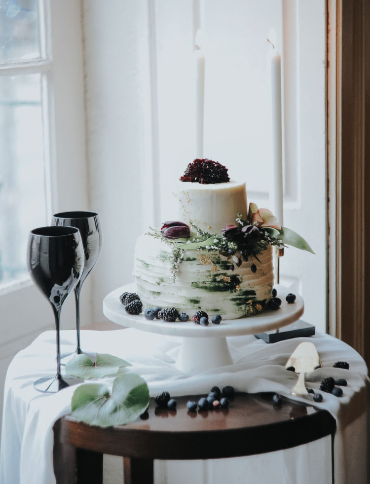 The textural wedding cake was topped with leaves, berries and dark purple blooms