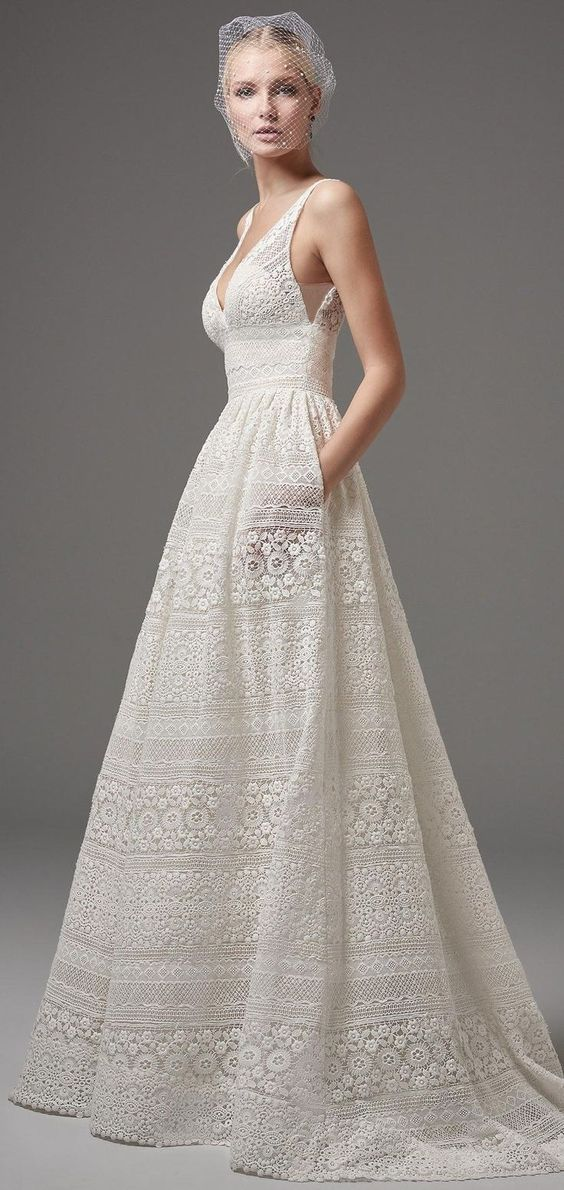 boho-inspired lace wedding dress featuring sheer pockets and patterns of eyelet lace, floral motifs