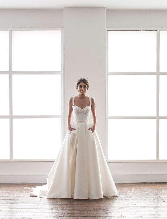 modern wedding dress in cream with a bustier and a full skirt with pockets
