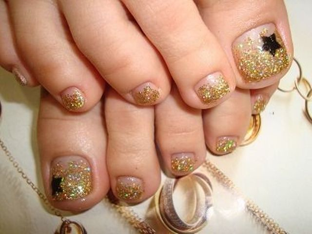 gold glitter nails with black star accents