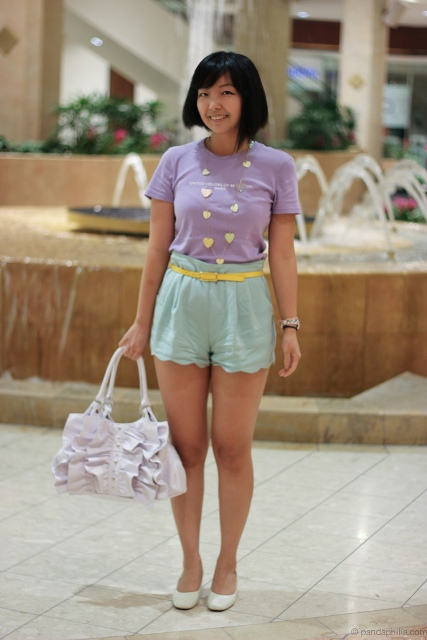 With purple shirt, yellow belt, white flats and bag