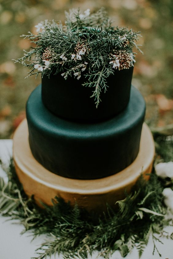 black and copper wedding cake topped with flowers and herbs