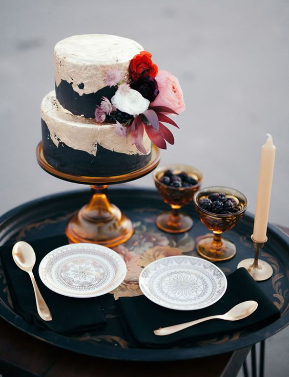 matte black and silver leaf cake with lush fresh blooms and berries