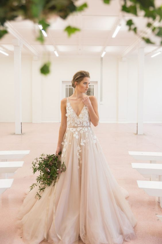 blush tulle wedding dress with white floral appliques on the bodice and partly on the skirt