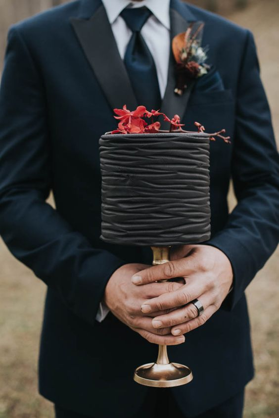 textural black wedding cake topped with red flowers