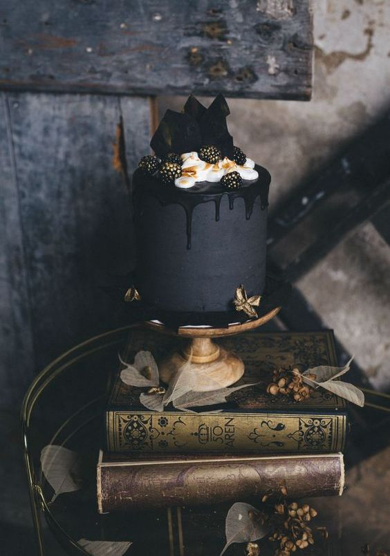 a matte black wedding cake with black drip, cream, gilded blackberries and chocolate on top