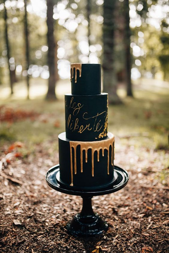 black wedding cake with copper drip and calligraphy