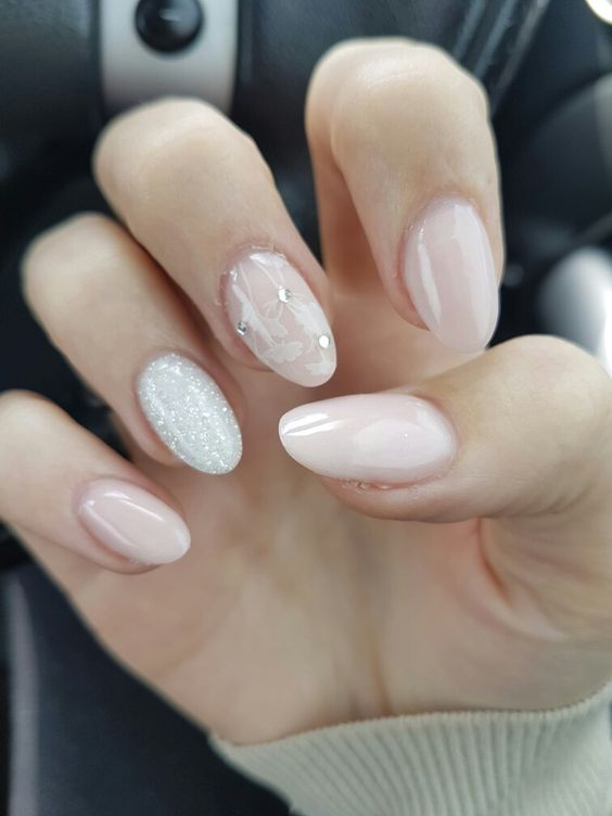 blush manicure with white glitter and rhinestone accents